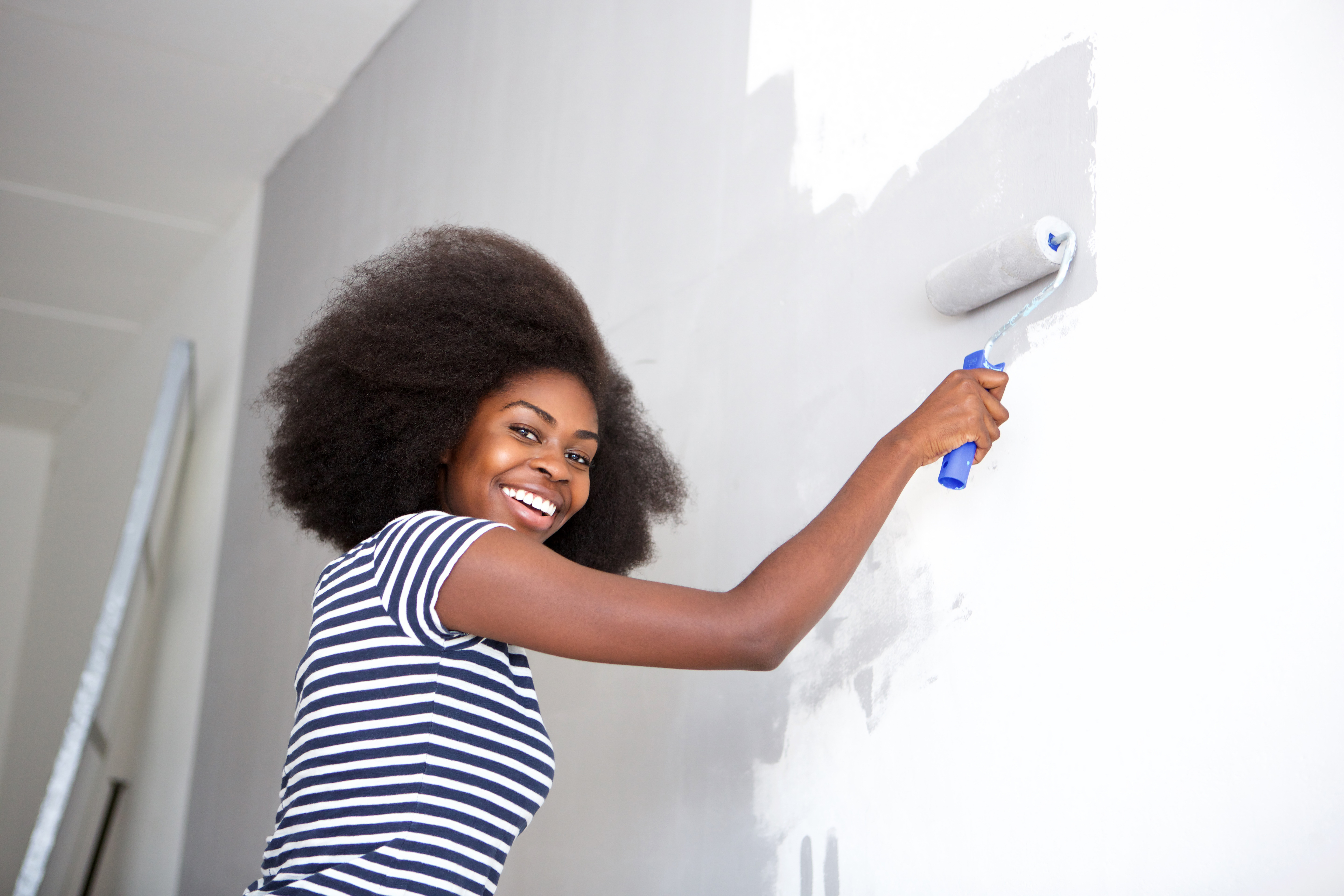 Side portrait of young african american woman painting wall at home